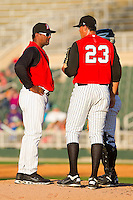 Kannapolis Intimidators pitching coach Jose Batista #38 has a chat with Chase Cooney #23 during the South Atlantic League game against the Hickory Crawdads at Fieldcrest Cannon Stadium on April 17, 2011 in Kannapolis, North Carolina.   Photo by Brian Westerholt / Four Seam Images
