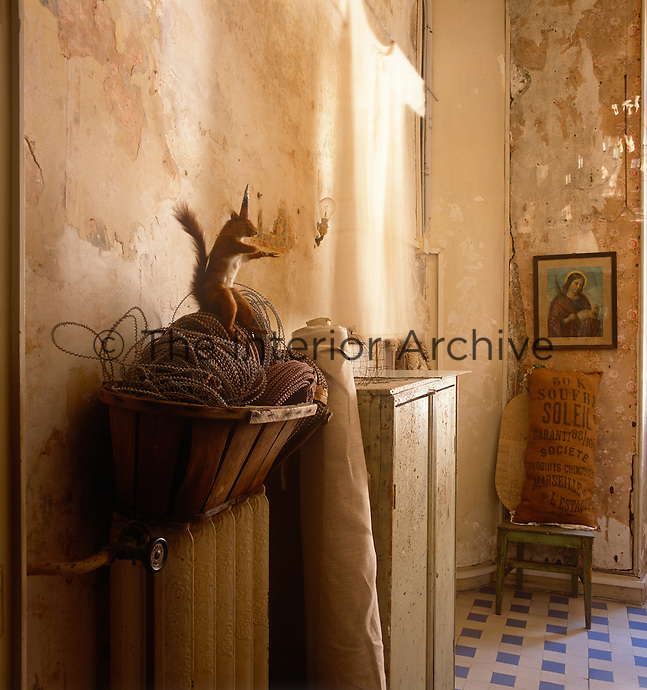 A hallway with a distressed plaster finish and a checked tiled floor. A cupboard stands to one side.