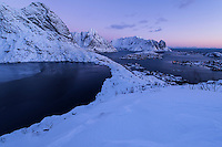 Winter sunrise over Reine and Olstind mountain peak from lake Reinevatnet, Moskenesøy, Lofoten Islands, Norway