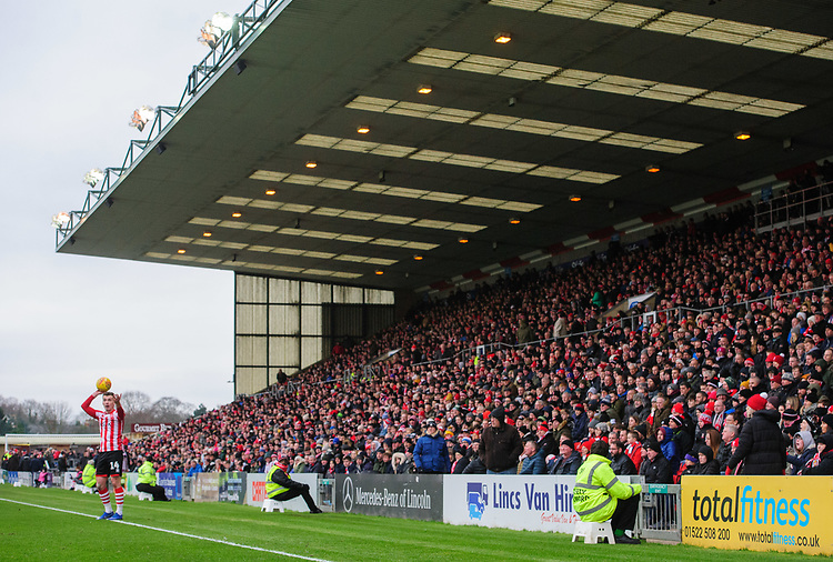 Lincoln City's Harry Toffolo takes a throw in, in front of the Lincoln City fans in the Lincolnshire Co-operative stand<br /> <br /> Photographer Chris Vaughan/CameraSport<br /> <br /> The EFL Sky Bet League Two - Lincoln City v Grimsby Town - Saturday 19 January 2019 - Sincil Bank - Lincoln<br /> <br /> World Copyright © 2019 CameraSport. All rights reserved. 43 Linden Ave. Countesthorpe. Leicester. England. LE8 5PG - Tel: +44 (0) 116 277 4147 - admin@camerasport.com - www.camerasport.com