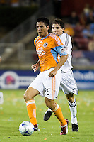 Houston Dynamo forward Brian Ching (25) passes the ball out of reach of  D.C. United defender Dejan Jakovic (5).  Houston Dynamo defeated D.C. United 4-3 at Robertson Stadium in Houston, TX on August 1, 2009.