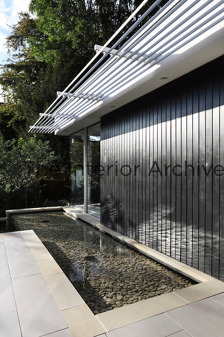 A modern house with a panelled facade and a full height window.  A clear water pool runs alongside a paved terrace.