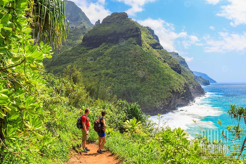 Two hikers on the Kalalau Trail near Hanakapi'ai Beach admire Kaua'i's Na Pali (or Napali) coastline.