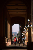Budapest, Hungary. Three people with bags on their back walking under an arch.