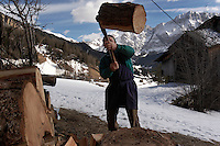 A Ladino man splits wood to warm the house he shares with a brother and sister in the Dolomites of Italy.  The unmarried siblings live together farming on property that has been in the family for generations.  La Valle is made up of a Ladino culture where the people have their own language.  They have close ties to the old ways--still using a horse and sled for spreading fertilizer.
