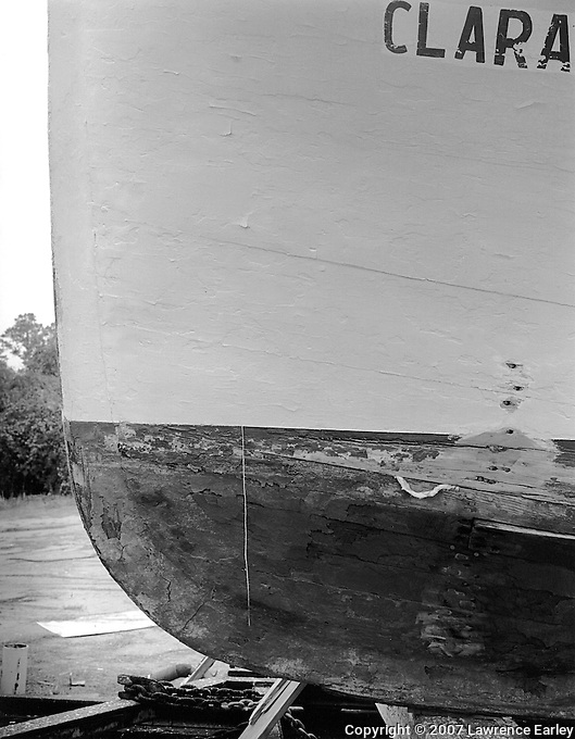 "Down East boatbuilders built ""wood to wood."" That is, they carefully fitted each plank to its neighbor using only a piece of cotton yarn as caulking. In this detail of the CLARA JOYCE undergoing repairs, note the yarn emerging from the seam. The string hanging at left was originally stretched from the stem to the stern along the hull to mark the waterline."