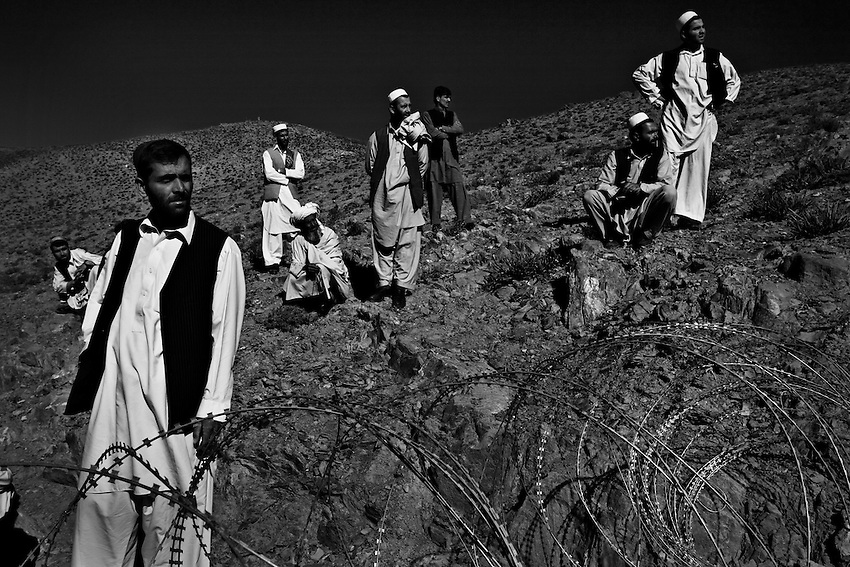 Afghans wait to be searched, finger-printed and have their retinas scanned at a checkpoint along a mountain road in the Kherwar Valley, Afghanistan, Friday, May 22, 2009.