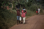 Children carries water over head along a road. In many developing countries children seen in the need to work to have access to the most basic things, help their families, go to school, food or water are just some of them.