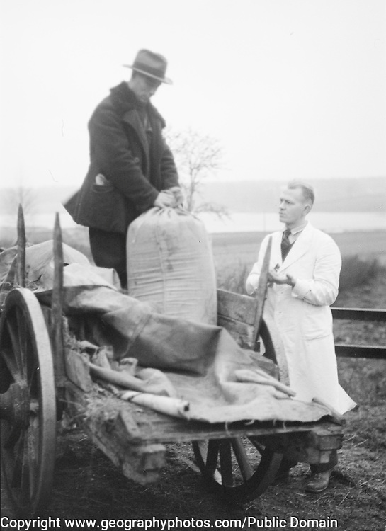 Farmer with sack on back of cart with man in white coat Finland 1920s- 1930s