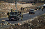 Israeli soldiers move along a road while palestinian activists they facing with them in the checkpoint of Beyt Furik in Nablus, West Bank. The palestinians claim the end of the israeli occupation in the West Bank.