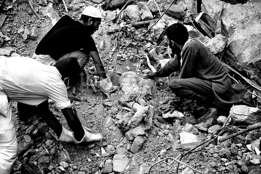 Rescue workers tries to find the remains of the garment worker, who died inside the rubble of the collapsed Rana Plaza building. Savar, near Dhaka, Bangladesh