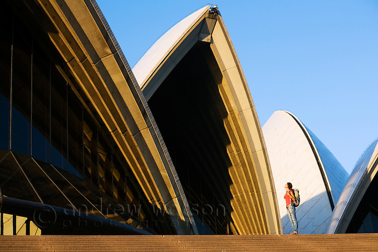 A tourist stands beneath the iconic roofs of the Sydney Opera House.  Sydney, New South Wales, AUSTRALIA.