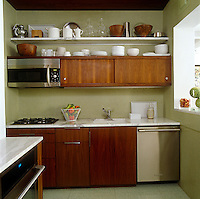 The kitchen has been lined with olive green mosaic tiles and the cupboards have been custom-made in warm walnut