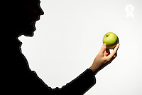 Silhouette of man holding green apple with mouth wide open (Licence this image exclusively with Getty: http://www.gettyimages.com/detail/sb10068346az-001 )