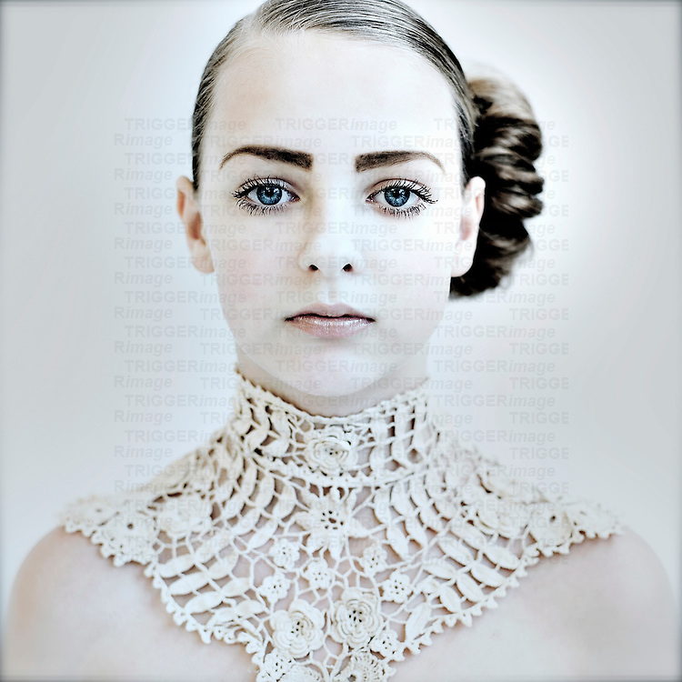 Close up head shot of young woman's face with blue eyes and decorative lace neck piece looking at camera