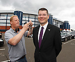SPL Chief Neil Doncaster getting miked up outside Hampden by Sky TV technician Ivan Coyle for his live interview after the SPL AGM