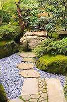 Stone walkway  with river stones leads to well in Portland Japanese Garden strolling garden.  Lantern seen in background amoung trees and rhododendrons and azaleas.
