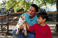 HISPANIC FATHER AND SON AT THE PETTING ZOO WITH BABY GOAT. FATHER AND SON. OAKLAND CALIFORNIA USA.