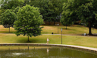 A man walks around the lake at Freedom Park in the Myers Park neighborhood in Charlotte, NC. Myers Park is one of the premier neighborhoods in North America and known for its large canopy of trees.
