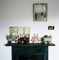 A collection of items are arranged on the mantelpiece of a simple black fireplace. A small mirror hangs above.