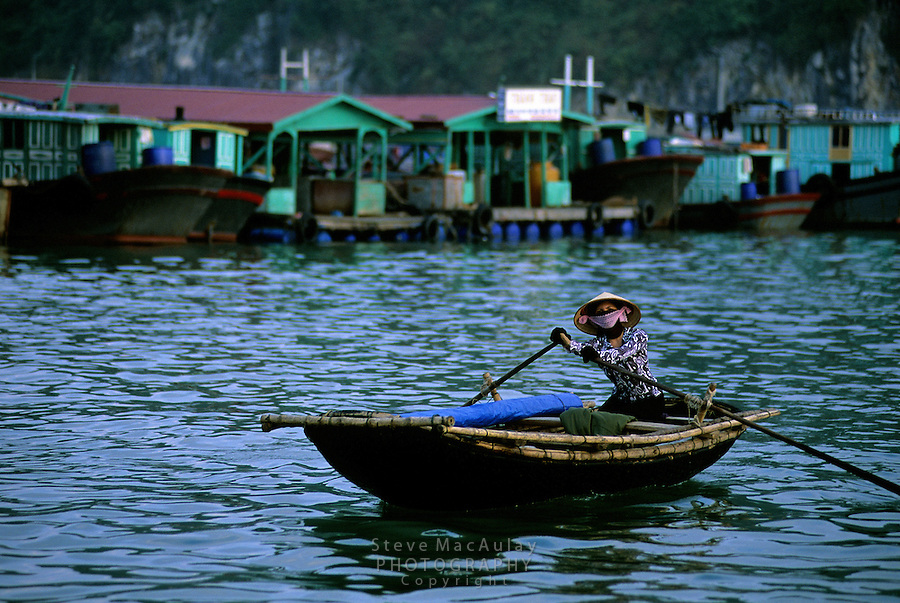 Woman in conical hat and face scarf, rows boat past floating homes, Halong Bay, Vietnam