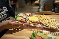 A server brings an order of a Classic Smashburger and fries to the table at the new Smashburger restaurant in the shadow of the Empire State Building in New York on its grand opening day, Thursday, April 10, 2014. The popular Colorado chain, which has a cultish following, opened its first Manhattan outpost  bringing their burgers, smashed to order to the Big Apple. The fast casual restaurant has a loyal fan base and has 260 restaurants worldwide. The franchise welcomed their Manhattan customers by offering a free Classic Smashburger to each patron all day, with the line eventually stretching around the block.  (© Richard B. Levine)