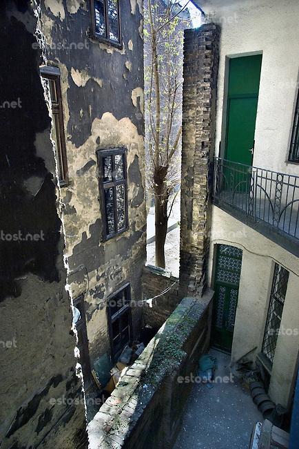 """UNGARN, 04.2009, Budapest - VII. Bezirk. Reste der Ghettomauer (Judenvernichtung 1944/45) im  alten Juedischen Viertel der Elisabethstadt (Erzsébetváros):  Die Mauer auf dem Hinterhof der Kiraly utca 51 riegelte das Haus links ab (Akacfa utca 62). Gut sichtbar ist hier, wie die alte Hofmauer erhoeht wurde. Vorne links erkennt man die rausgeschlagenen Ziegel fuer die Aufnahme der Hochmauer. Die Ghettogrenze verlief in Budapest nicht entlang von Strassen, sondern wurde hinter den Haeusern ueber Brandwaende und entsprechend verstaerkte Hofmauern gefuehrt, was Aufwand und Sichtbarkeit minimierte.   Remains of the Ghetto wall (Holocaust 1944/45) in the old Jewish quarter of the """"Elizabethtown"""" district: The wall in the backyard of Kiraly street 51 cut off the adjacent house to the left (Akacfa street 62). Here the elevation of the old courtyard wall is clearly seen. In the front to the left the torn out brick joints are visible, providing stability to the add-on wall. The ghetto boundary in Budapest did not follow open streets, but was drawn behind the houses using party walls and reinforced courtyard walls, thus minimizing effort and visibility..© Martin Fejér/EST&OST"""