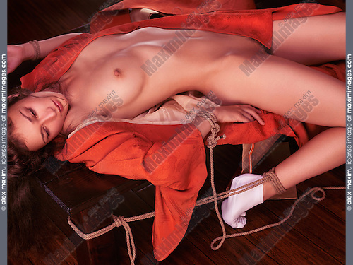 Beautiful young woman in red kimono lying naked on a table tied with sensual Japanese bondage Shibari