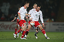 Michael Bostwick and Joel Byrom of Stevenage hold off Luke Chadwick of MK Dons . - Stevenage v Milton Keynes Dons - npower League 1 - Lamex Stadium, Stevenage - 24th January 2012. © Kevin Coleman 2012