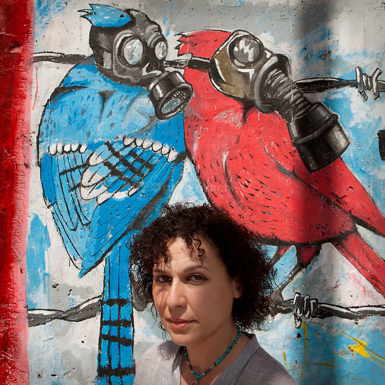 """Egypt / Cairo / 6.4.2013 / Heba Helmy, Egyptian grafic designer, poses in front of graffiti in Mohamed Mahmoud Street in Downtown, Cairo. Heba documented the street art in the book """"Martyr inside me"""" (Gowaya chahid). © Giulia Marchi"""