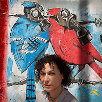 "Egypt / Cairo / 6.4.2013 / Heba Helmy, Egyptian grafic designer, poses in front of graffiti in Mohamed Mahmoud Street in Downtown, Cairo. Heba documented the street art in the book ""Martyr inside me"" (Gowaya chahid). © Giulia Marchi"