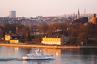 An evening view over Stockholm Strom Strommen with an old style passenger ferry boat Djurgarden on the water in front of Kastellholmen and Ostermalm in the background Sun reflections in the water Stockholm, Sweden, Sverige, Europe