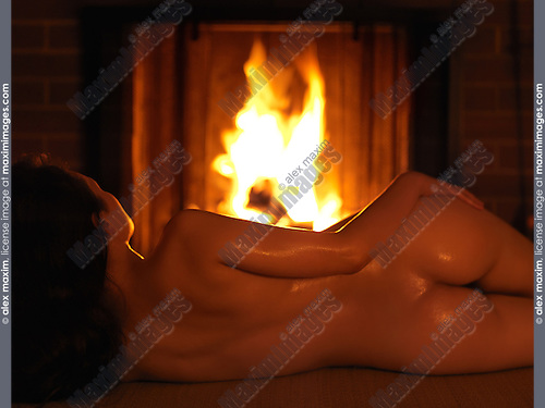 Beautiful woman lying naked in front of a burning fireplace with her back to the camera