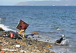 A Greek fisherman scavenges a boat and motor that remain after the beaching of a refugee boat that arrived on a beach near Molyvos, on the Greek island of Lesbos, on November 2, 2015. It crossed the Aegean Sea from Turkey, carrying refugees from Syria, Iraq, and elsewhere who paid migrant smugglers huge sums for the trip.