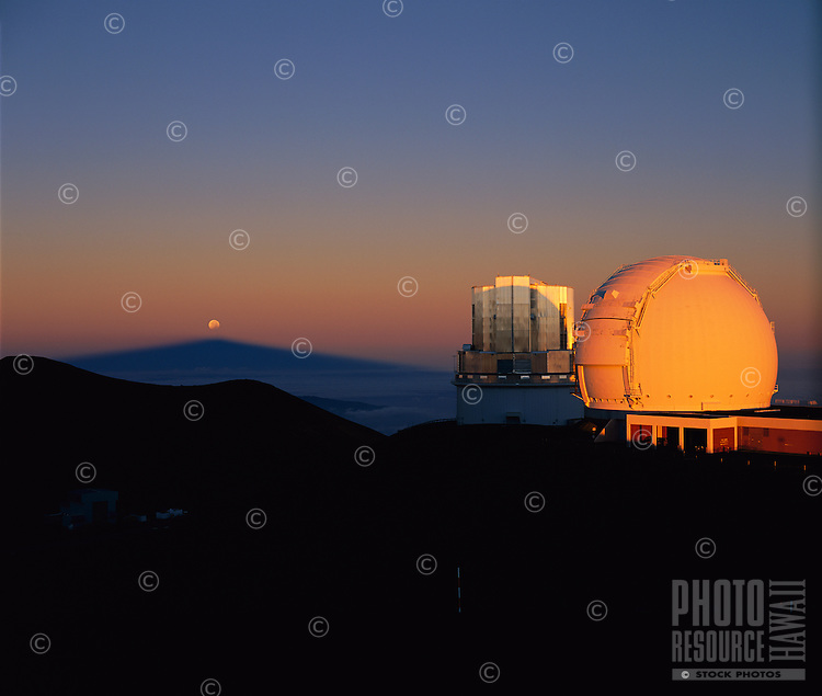 Keck 1 Telescope dome (right), Subaru Telescope enclosure (center) and partially eclipsed moon rising over the shadow of Mauna Kea on the Earth's Atmosphere, at sunrise, shortly after a total lunar eclipse.  Mauna Kea Observatory, Hawaii.