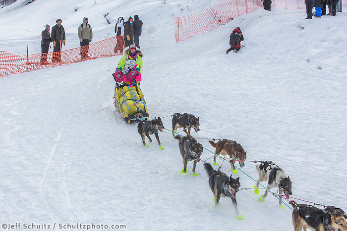 Monica Zappa from Kasilof, Alaska drops down onto the Chena River with her team shortly after the start of the 2015 Iditarod sled dog race. in Fairbanks. Photo by Todd Paris/IditarodPhotos.com 2015
