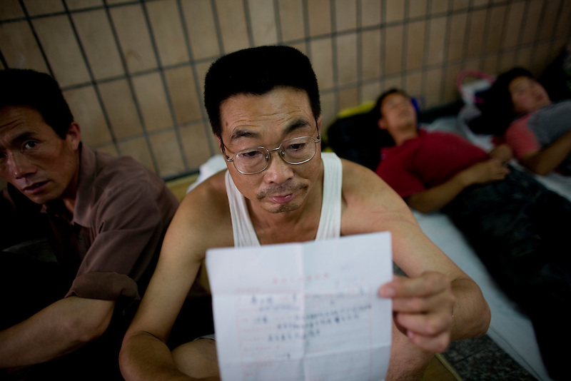 A man holds up documents describing his legal case as he sits in an underpass, in which he currently lives. The homes of petitioners, who were living near the Supreme Court of China, in southern Beijing were recently demolished ahead of the summer Olympics. Rather than return to their respective provinces, many of the petitioners have resorted to living on the streets, persisting in seeking legal justice.