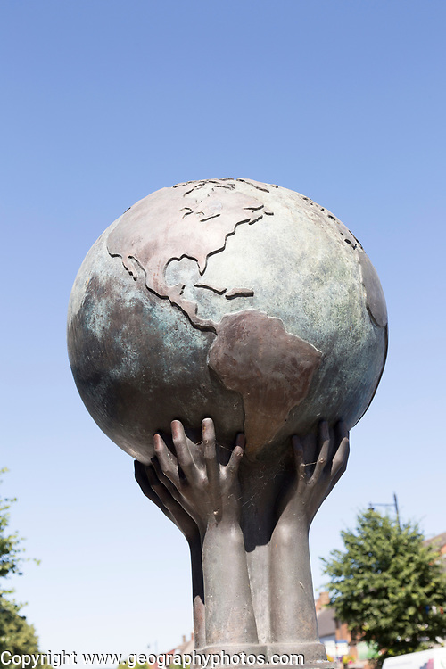 War memorial sculpture showing the world held by hands, Royal Wootten Bassett, Wiltshire, England, UK