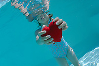 Girl (6-7) holding heart shaped symbol in swimming pool, underwater view