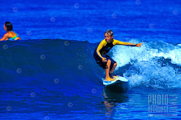 A young boy in a wetsuit surfs a smooth swell on a Maui beach.