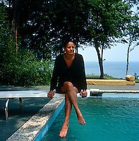 Portrait of designer Muriel Brandolini sitting on the diving board of her swimming pool
