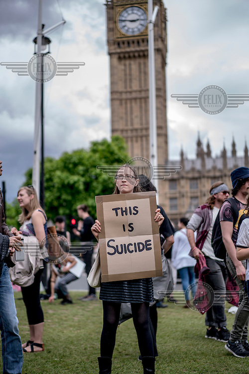 A woman holds a placard that reads: 'This is suicide' at a demonstration in Parliament Square protesting the victory of the 'leave' (the EU) side in the EU reeferendum.