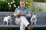 Man on park bench reading with two dogs