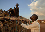 Ganun Butros Wadko (right) talks with Yoel Lipu as he puts a roof on his rustic home in the Doro Refugee Camp in Maban County, South Sudan. The camp is one of four in Maban that together shelter more than 130,000 refugees from the Blue Nile region of Sudan.<br /> <br /> Jesuit Refugee Service provides educational and psychosocial services to both refugees and the host community in Maban. Wadko, a refugee himself, is supervisor of the JRS psychosocial team's home visits in the Doro Camp.<br /> <br /> Misean Cara provides support for the work of Jesuit Refugee Service in Maban.