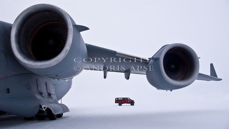 A truck is dwarfed by a C17 aircraft on McMurdo Ice Shelf. Antarctica.