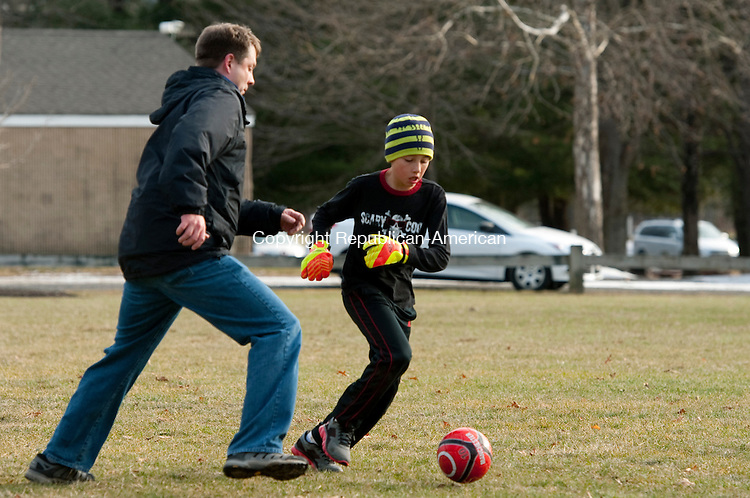 WATERBURY, CT-122713JS04- Aiden Colby, 10, of Woodbury, slips past his uncle Jason Johnston of Greenville, SC, as they play a pick-up soccer game with other family members Friday at Hollow Park in Woodbury.<br /> Jim Shannon Republican-American