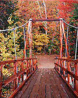 View looking down a foot bridge crossing the Pemigewasset River in the White Mountain National Forest. New Hampshire.