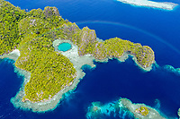 aerial view of a rainbow appears over a remote set of limestone islands, Raja Ampat Islands, West Papua, Indonesia, Pacific Ocean