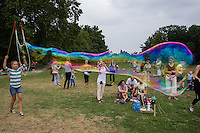 Girl blows a giant soap bubble during a soap bubble day in a public park in Budapest, Hungary on August 25, 2013. ATTILA VOLGYI