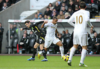 Barclays Premier League, Swansea City (White) V Norwich City (black) Liberty Stadium, Swansea, 08/12/12<br /> Pictured: Swansea's Wayne Routledge  skips through the tackle of Wes Hoolahan<br /> Picture by: Ben Wyeth / Athena <br /> Athena Picture Agency<br /> info@athena-pictures.com